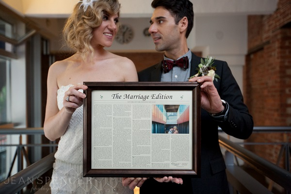 Newly married couple holding a newspaper article with their love story