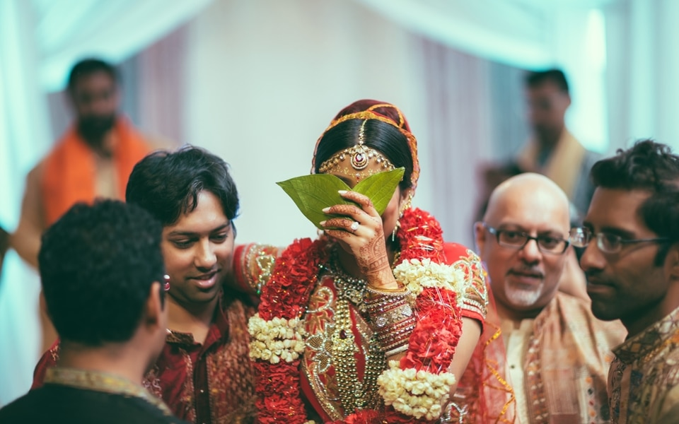 bride hides her face with leaves at indian wedding