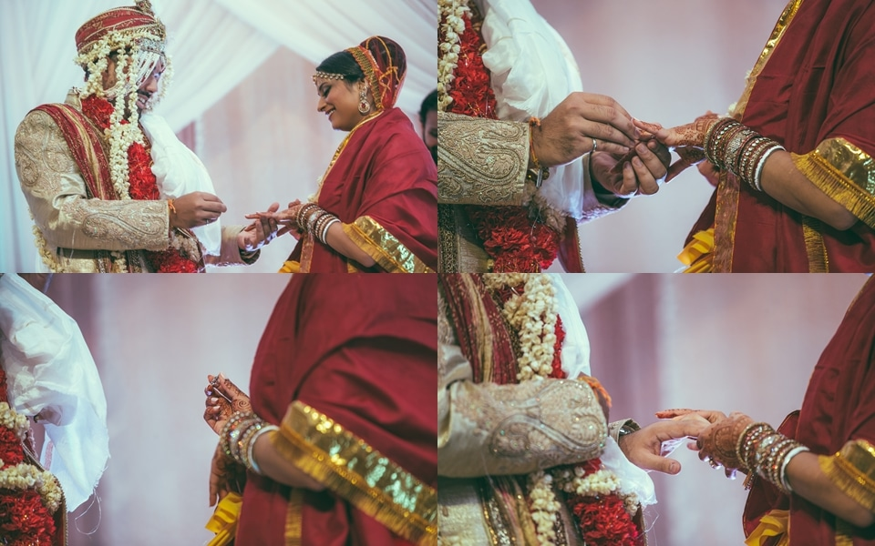groom places ring on brides hand at indian wedding