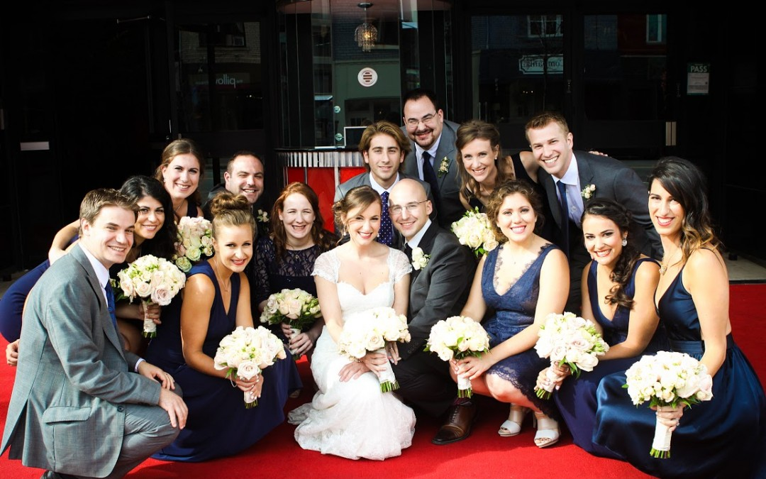 Bride and groom and bridal party posing for a picture in front of the Eglinton Grand in Toronto.