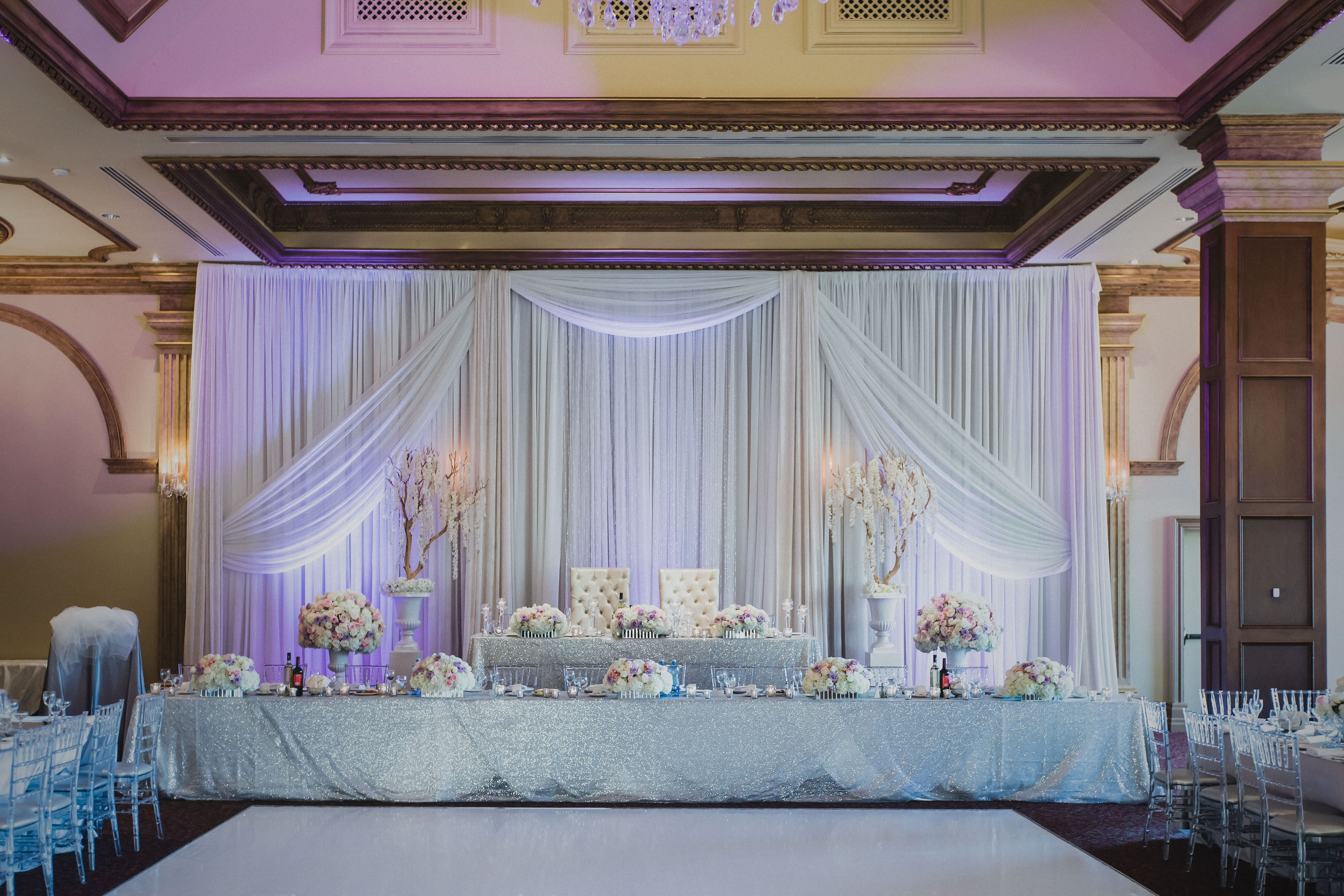 wedding head table and sweetheart table with floral arrangements