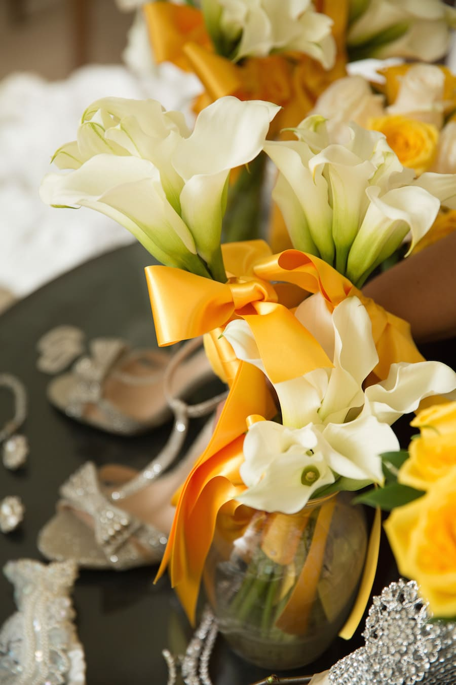 white calla lilies with a sunshine yellow ribbon in a metallic vase