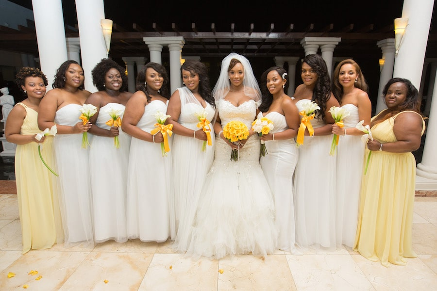bride with all of her bridesmaids dressed in white and yellow