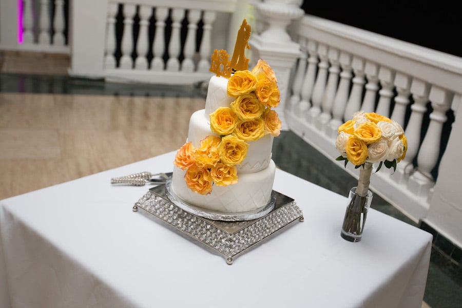cake adorned with yellow roses on sliver cake plate