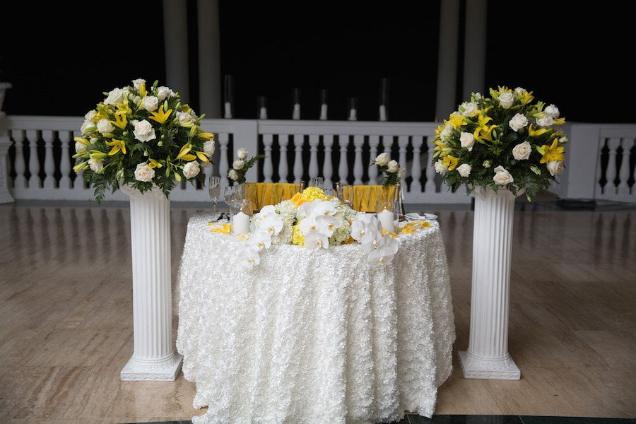 white and yellow sweetheart table featuring orchids and bouquets