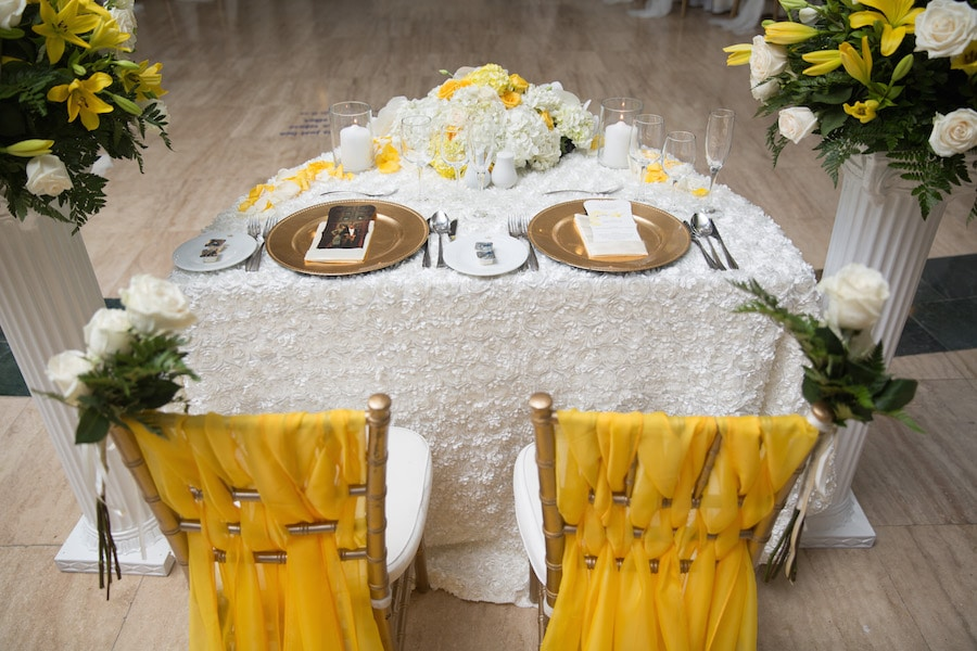 white and yellow sweetheart table with floral design and gold charger plates
