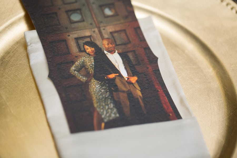 bride and groom photo on gold charger plate with white napkin