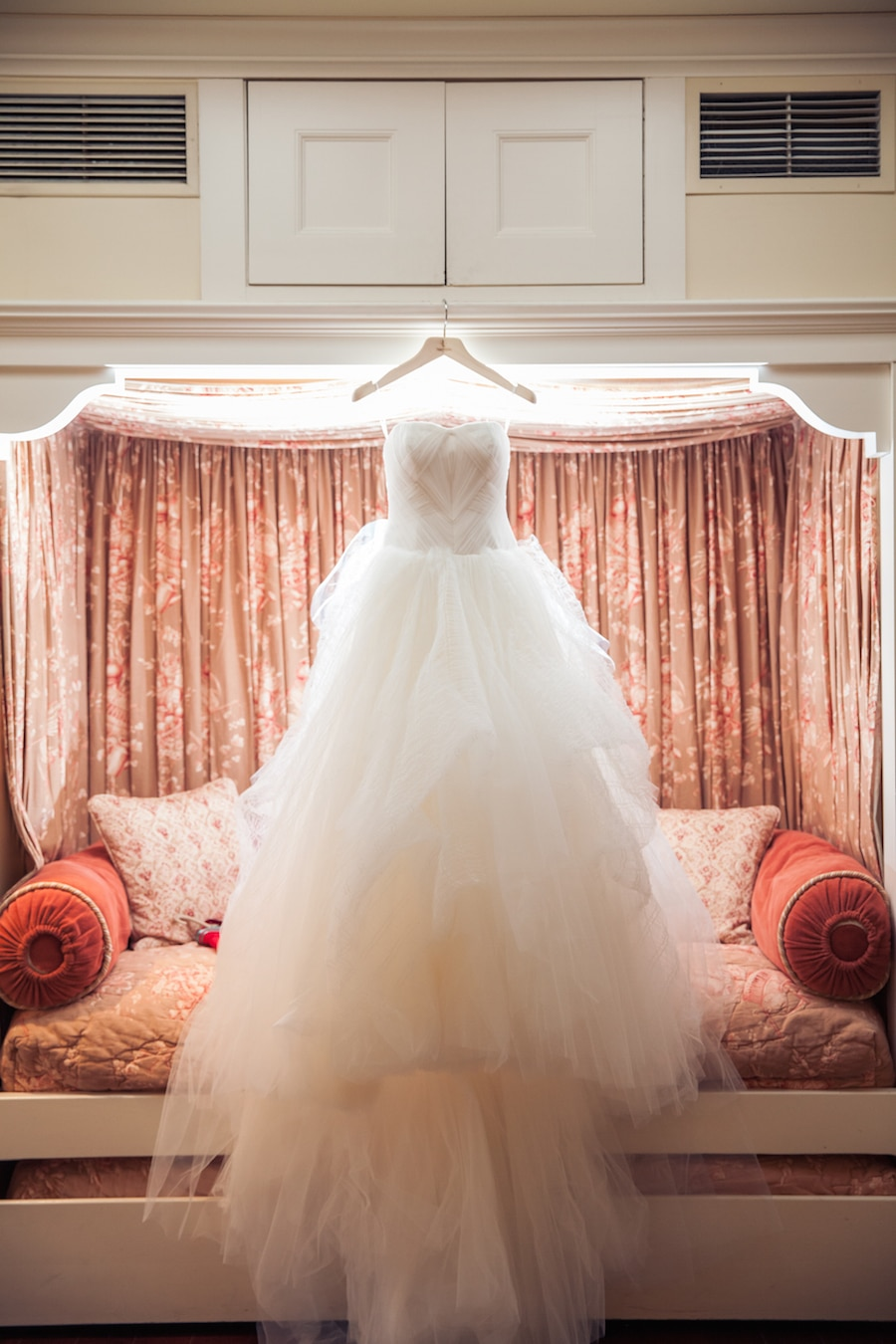 beautiful wedding gown hanging with light shinning through