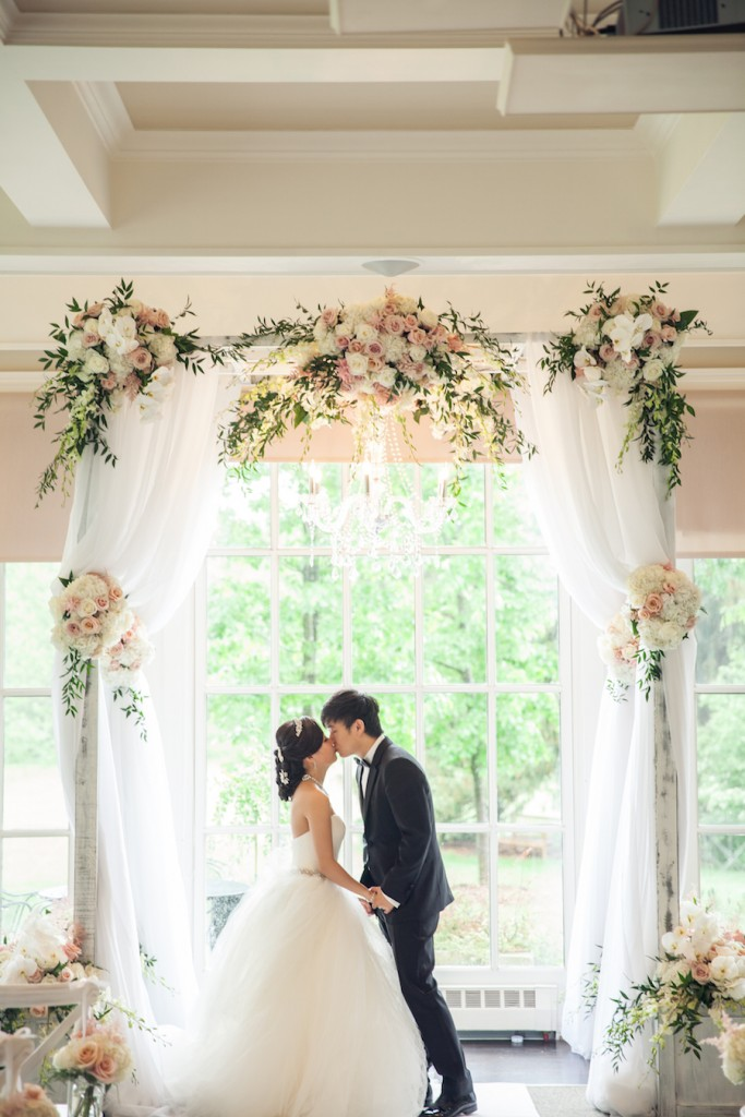 bride and groom kissing under ceremony canopy