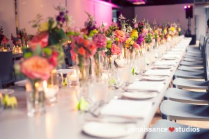 Clusters of vases with Flowers in varying heights along long rectangular table