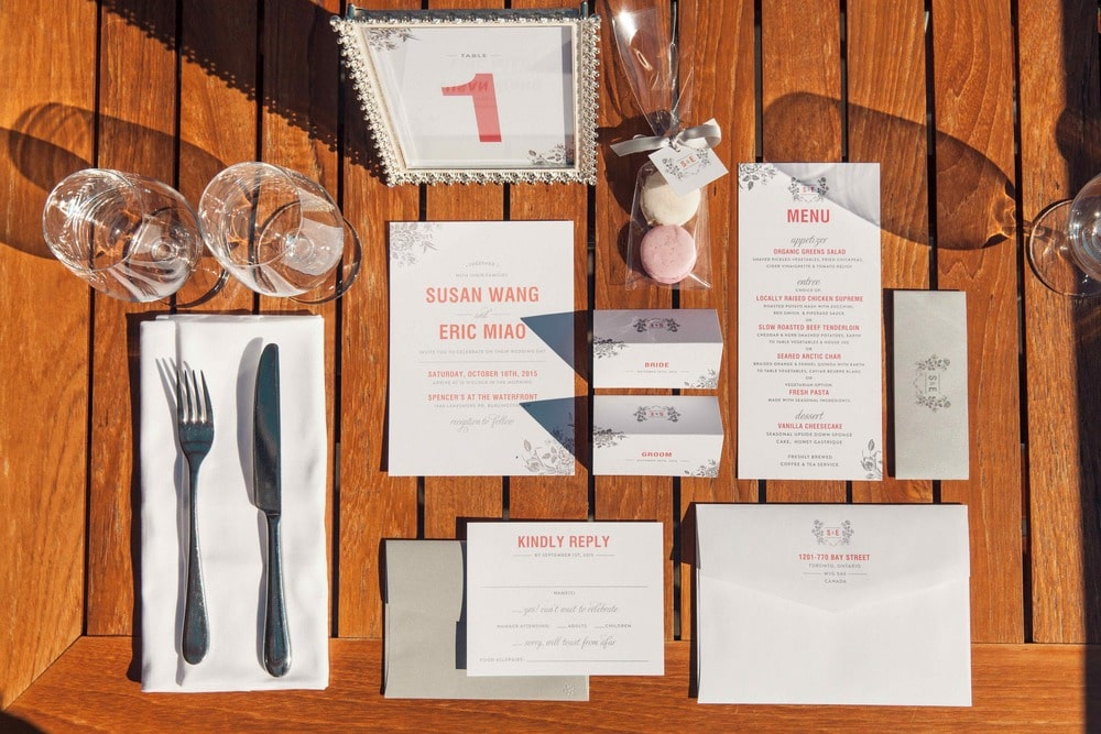 pink invitations with silver accents on wooden table