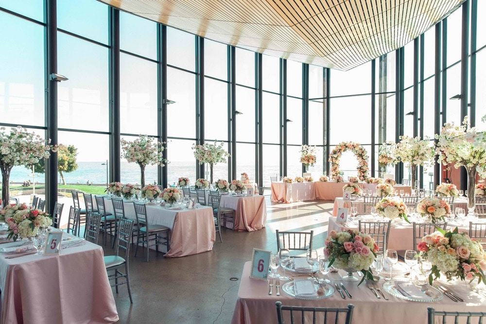 pink pastel themed wedding reception with rose centrepieces and floral arch