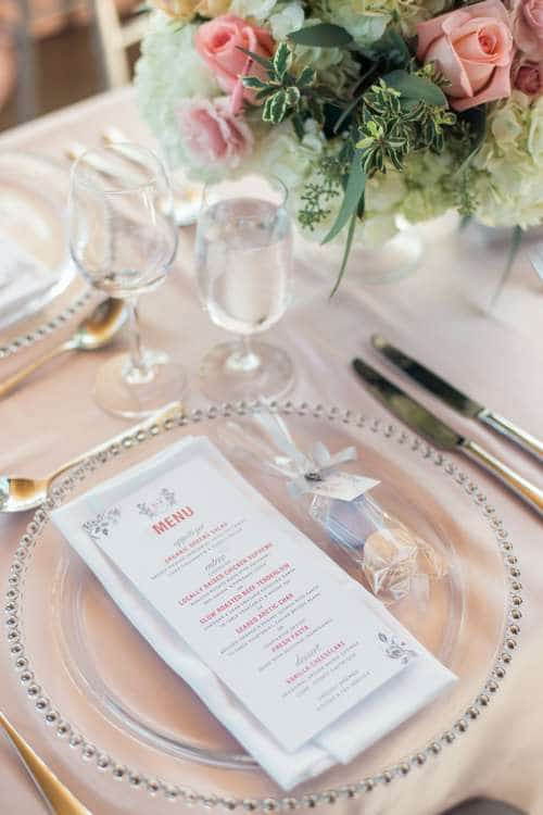 sliver and pink menu on a transparent charger plate with bouquet