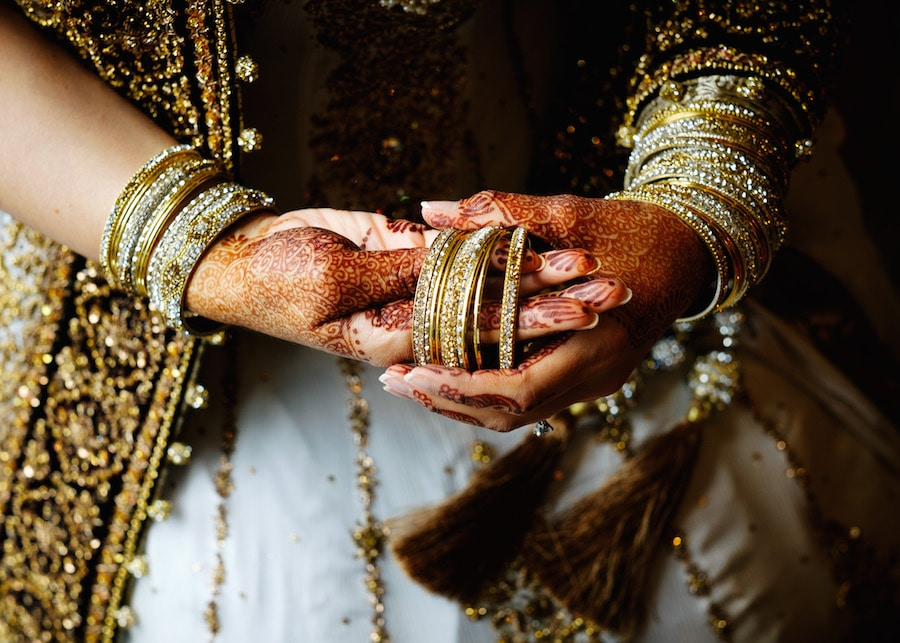 The bride is putting on her many bracelets over her Mehndi covered hands.
