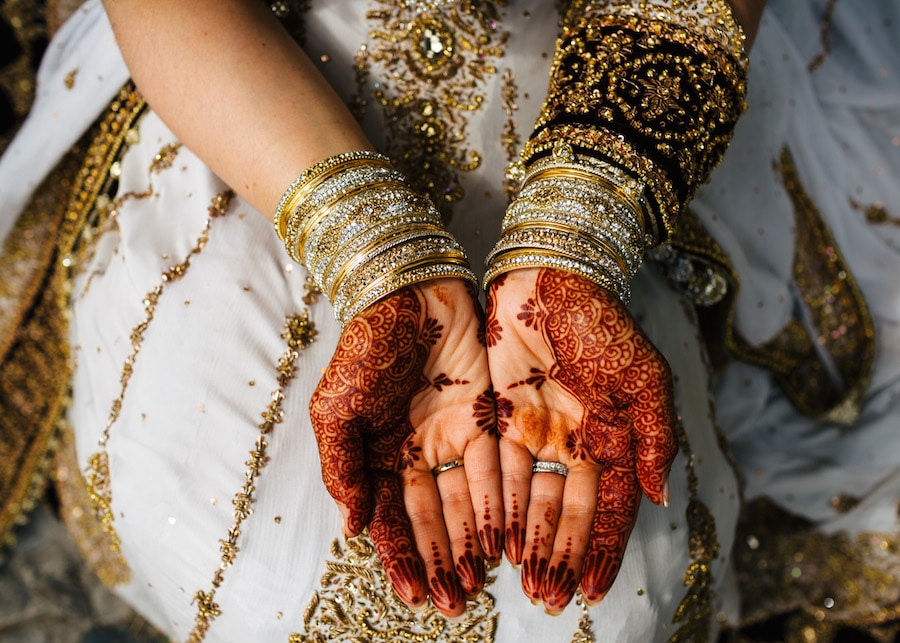 The bride is sitting down showing a bit of her dress, accessories and especially her beautifully designed Mehndi hands palm up.