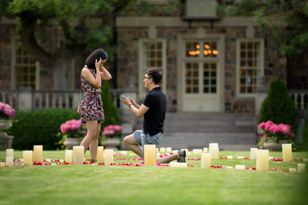A man on one knee proposing to a woman in a garden surrounded by flower pedals and candles