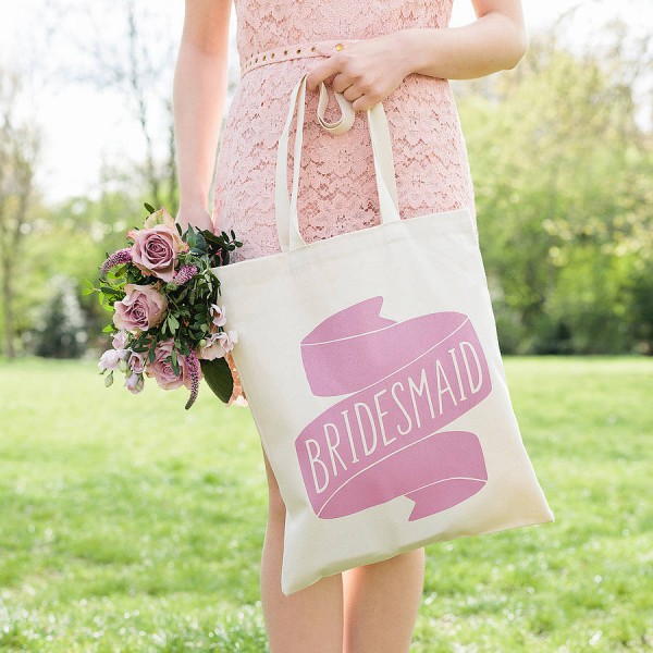 "bridesmaid holding a bouquet and a tote bag reading ""bridesmaid"""