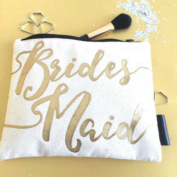 "white makeup bag with the writing ""bridesmaid"" on it"