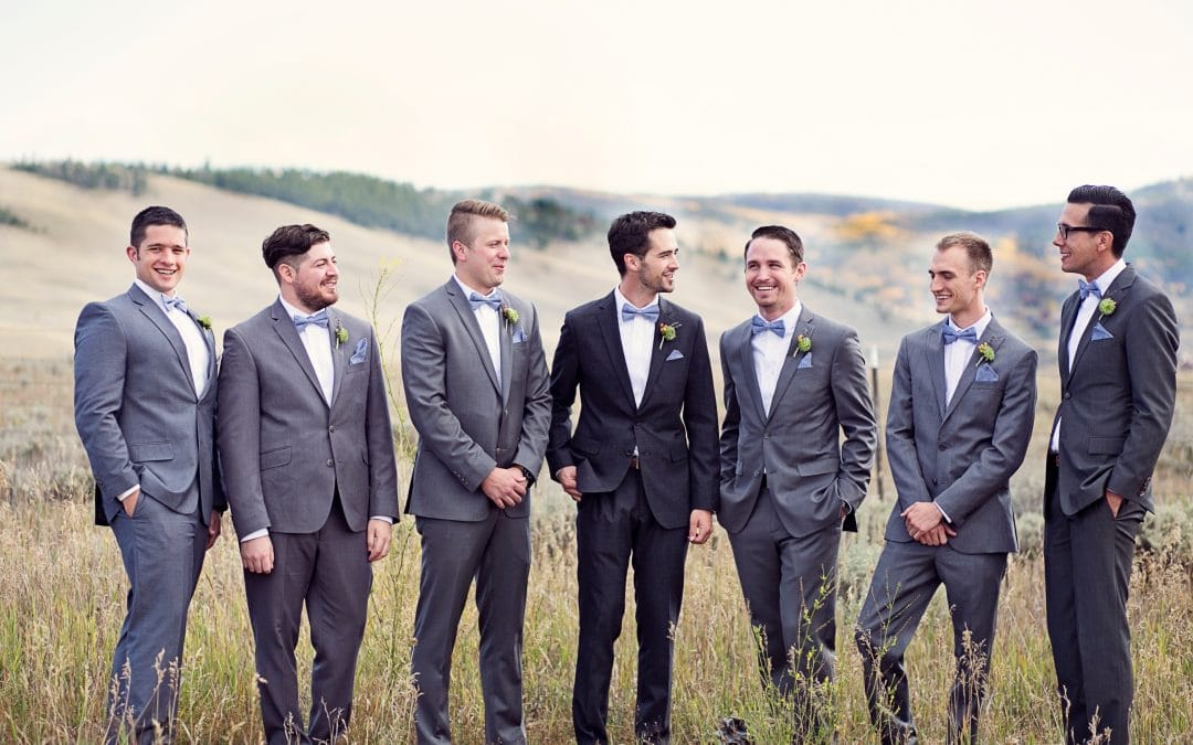 A groom and his groomsmen standing in a field looking at eachother