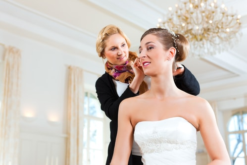 bride getting her hair done in an updo for her wedding